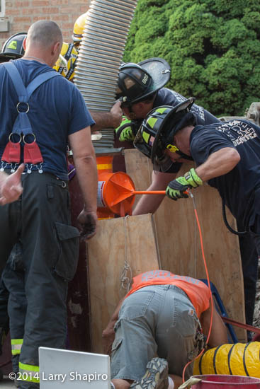 firemen use a rescue vac to rescue worker trapped in a trench