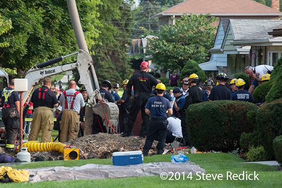 firemen work to free a worker trapped in a trench