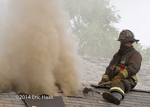 firemen with axes venting house with peaked roof in Chicago during a fire