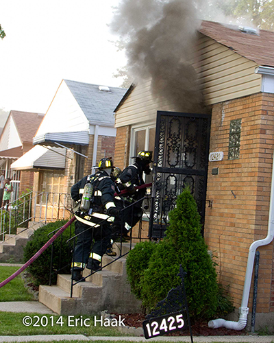 firemen enter a house with thick smoke coming out