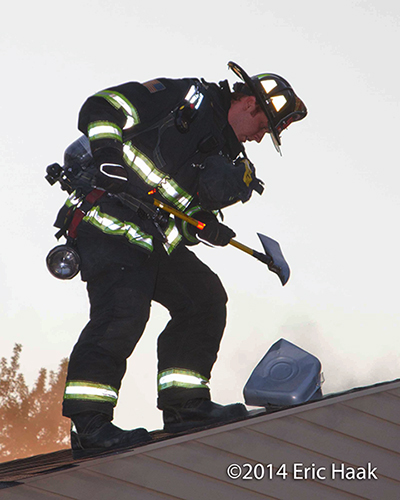 fireman on the roof of a house with an ax