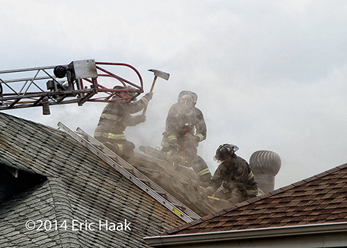 fireman with axe venting roof at house fire