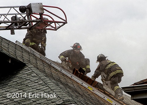 firemen venting roof at house fire