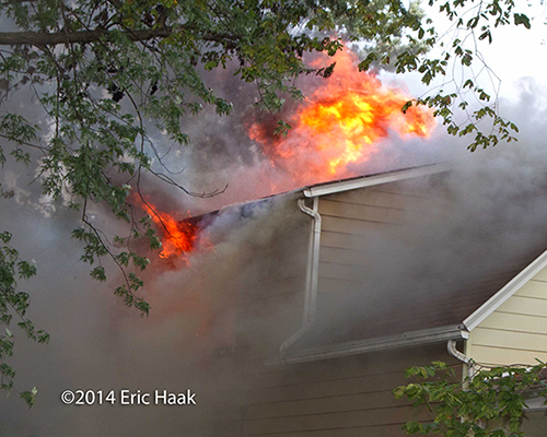flames through the roof of a house on fire