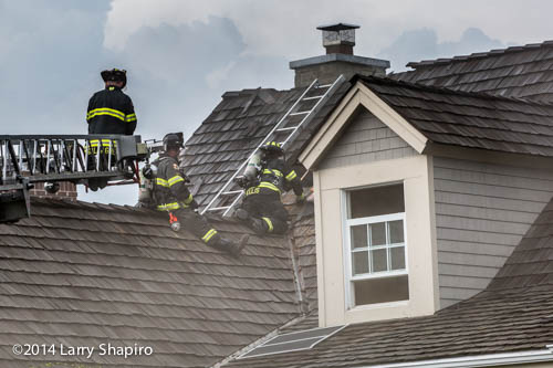 firemen vent roof of house