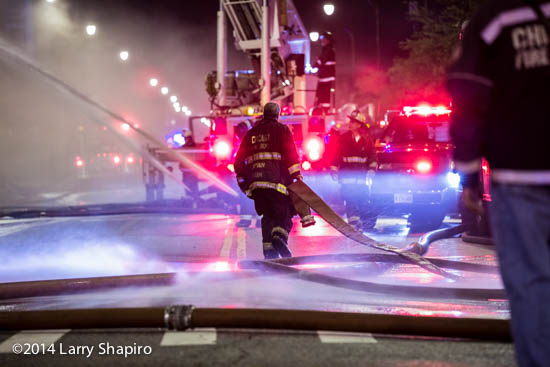 fireman pulling hose at night fire scene with lights