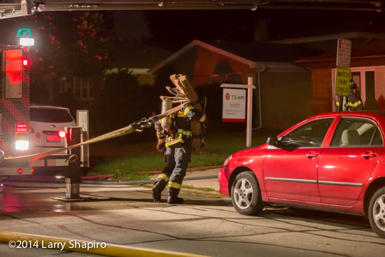 fireman pulls hose at night fire scene
