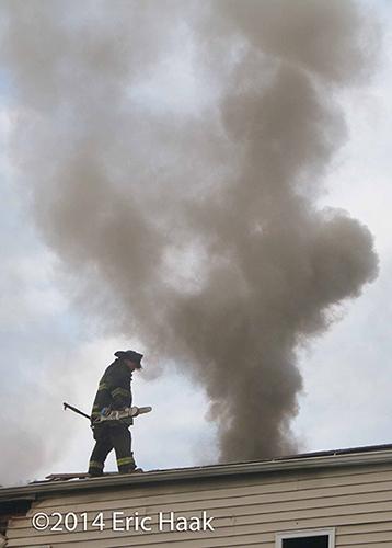 firemen net roof at smokey house fire