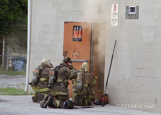 firemen mask up for entry into fire building