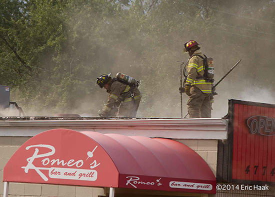 firefighters on flat roof venting a fire