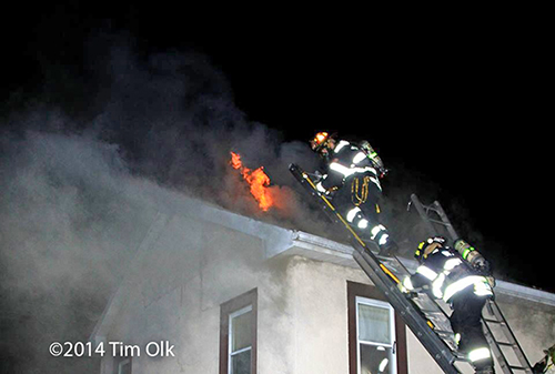firemen climb a ladder to the roof of a house on fire