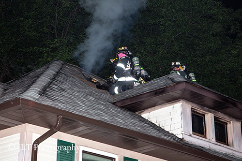 firemen vent roof at house fire