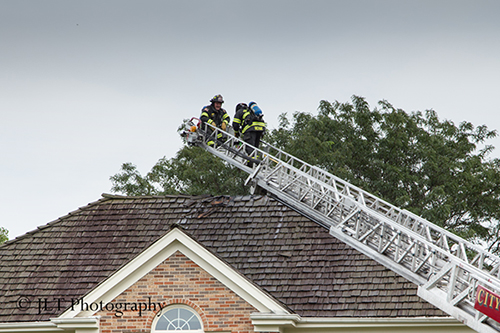 firemen on aerial ladder at house fire