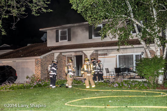 smoke pushes from a house at night as firefighters prepare to enter