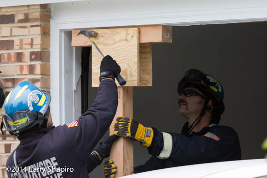 firefighters work to shore up a house damaged after an accident