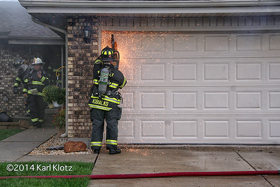 fireman cuts garage door with saw