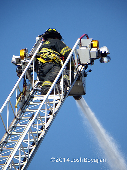 fireman working master stream from laerial ladder