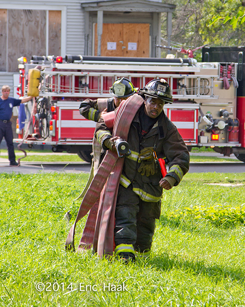 fireman carrying hose on his shoulder