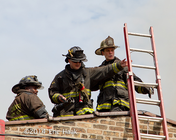 firemen on a roof at fire scene