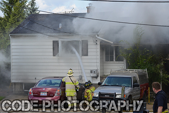 firemen with a hose line at a house fire