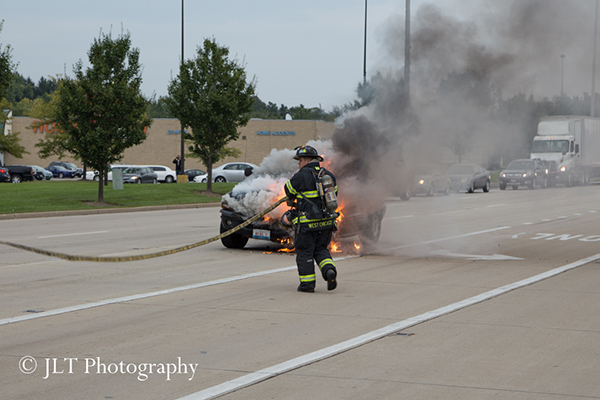 firemen approach a car on fire in the street