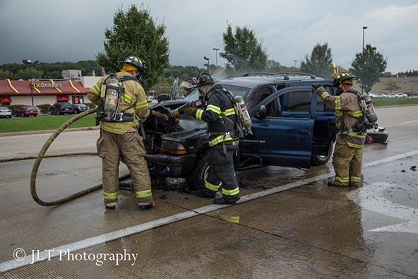 firemen inspect car after fire