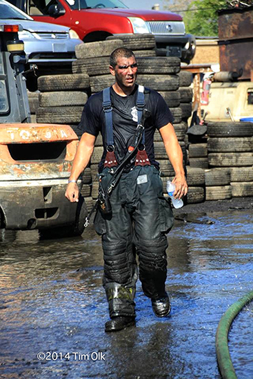 firefighter drenched from battling a fire on a hot day