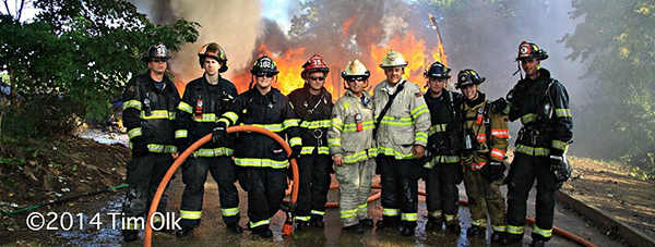 firemen posing in front of fire