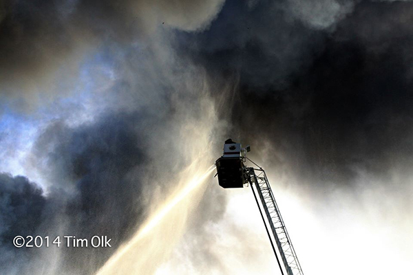 firemen in tower ladder bucket surrounded by smoke
