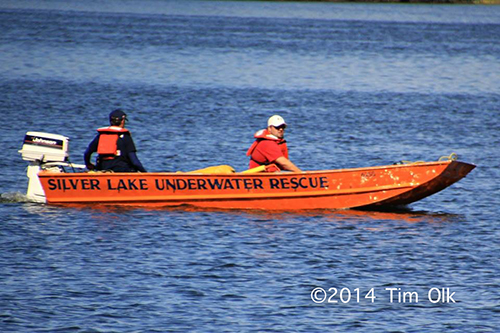 firemen in boat search lake for victim