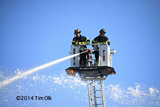 firemen in tower ladder bucket with master stream