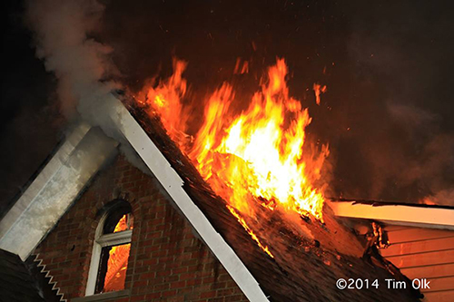 flames through the roof of a house