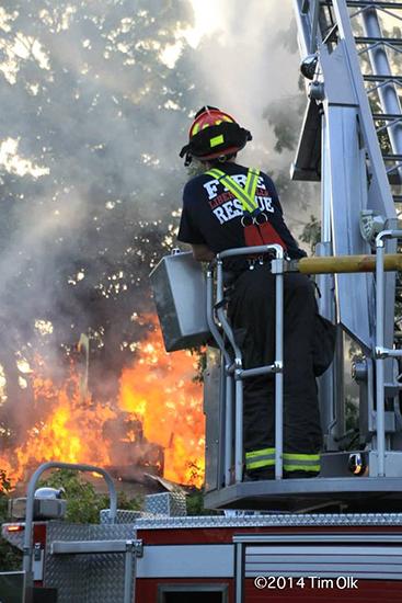 fireman operating ladder truck at fire scene