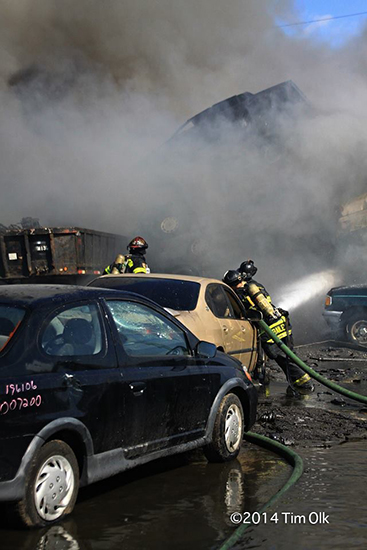 firemen working at a junk yard fire