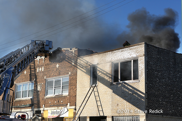 black smoke pours from the roof of a commercial building
