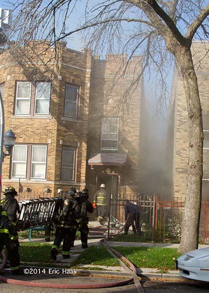 firemen carry ladder towards building fire
