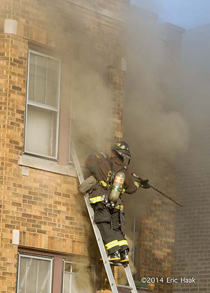 fireman on ladder with smoke venting window