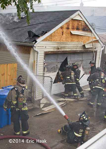 firemen cutting garage door at fire scene