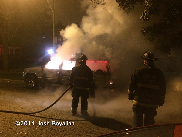 firemen extinguish car fire at night