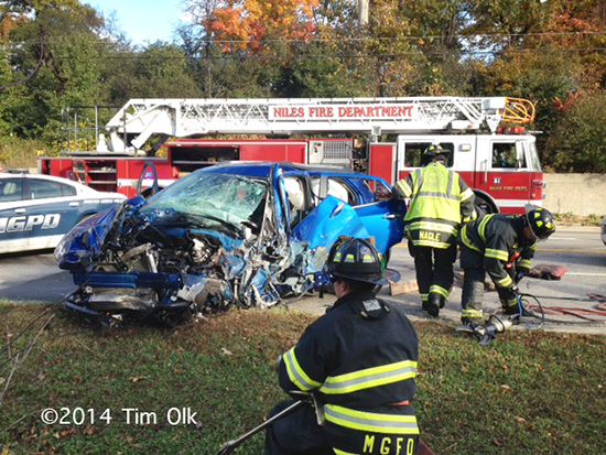 firemen work to free trapped driver from car