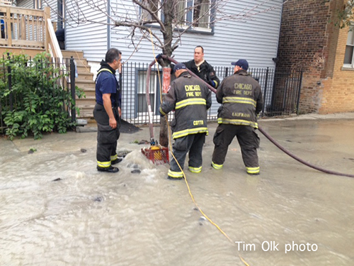 firemen pump water from street