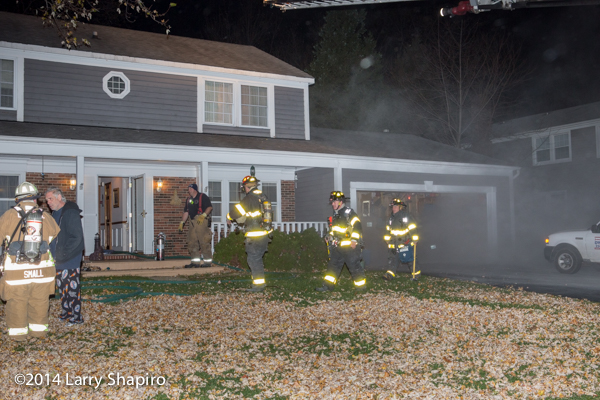 firefighters at residential house at night