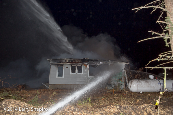 firemen pour water on a house destroyed by fire