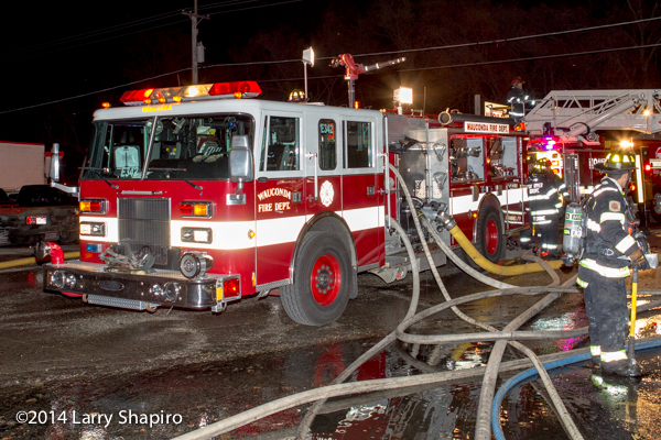 Pierce fire engine with many hose lines at fire scene