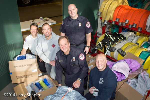 children receive free winter coats from firefighters