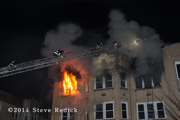 Chicago firefighters on aerial ladder with heavy fire and smoke
