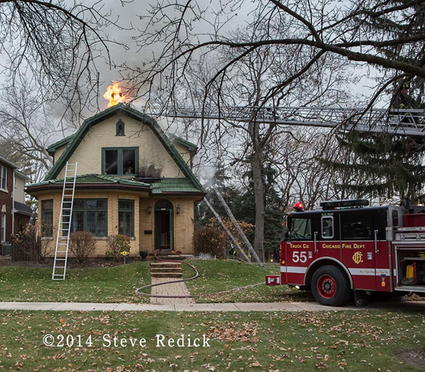 fire truck on scene with flames through roof of a house