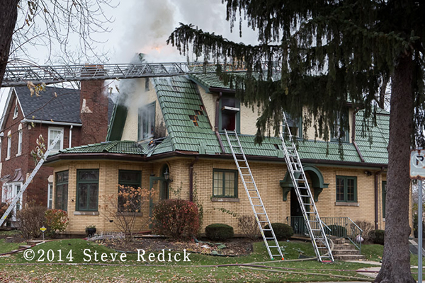 firemen place ladders to windows of house fire