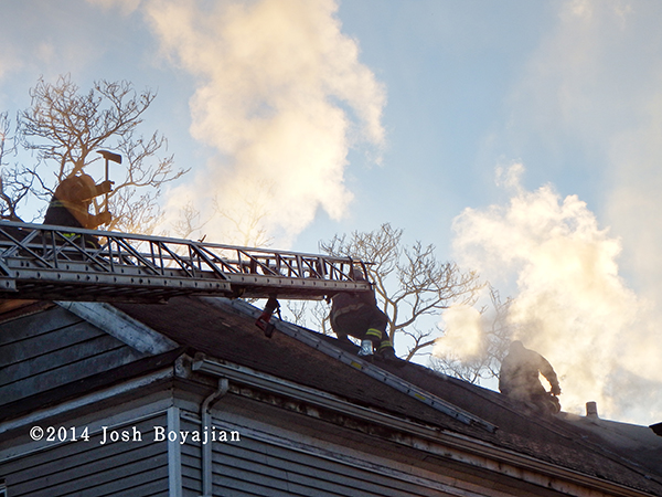 firemen on roof with aerial ladder
