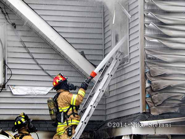firefighters with hose line at house fire